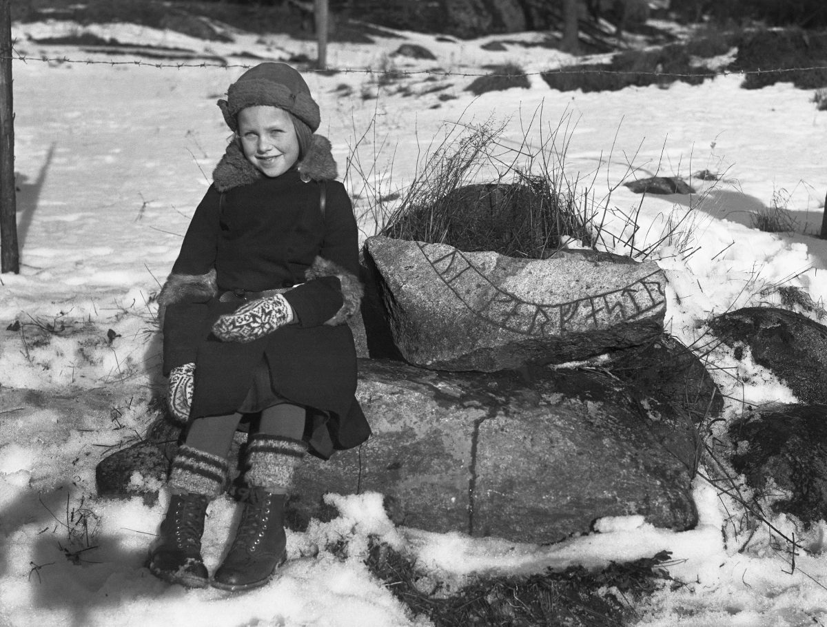 Girl by a fragment of a runestone found at Ekbacken. The inscription says Gerfast. 1935.jpg