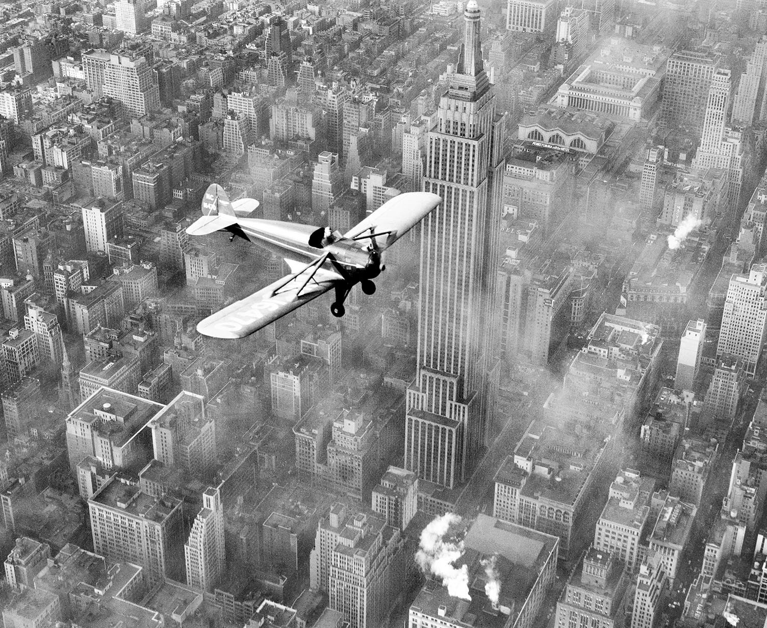 Ted Herbert, in his plane powered by a V-8 automobile engine, over midtown Manhattan in February 1937.jpg