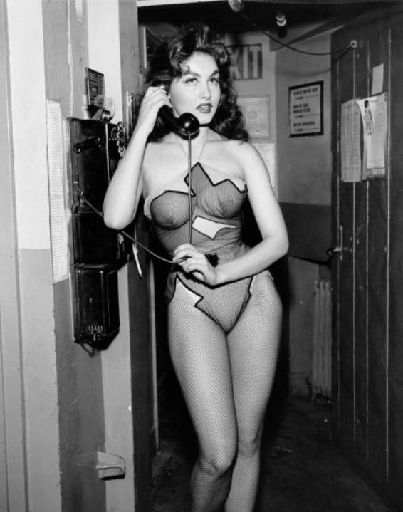 Julie Newmar in costume as Stupefyin' Jones taking a phone call backstage during a Broadway performance of Li'l Abner in 1956.jpg