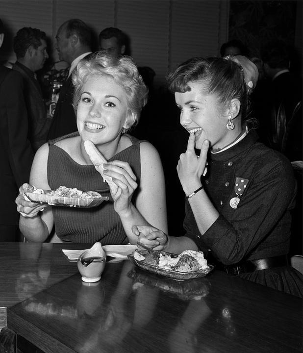 Kim Novak and Debbie Reynolds enjoying a banana at Schwabs Pharmacy in Hollywood, 1954.jpg