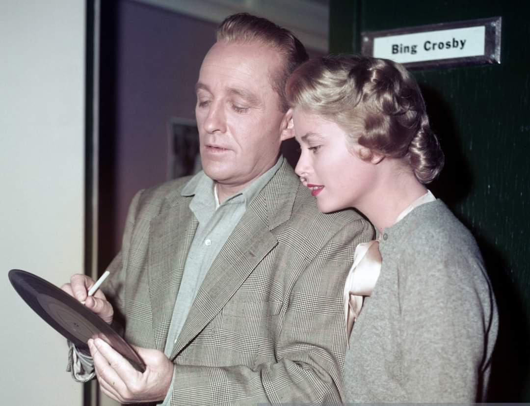 Bing Crosby autographs one of his records for co-star, and future Princess of Monaco, Grace Kelly, circa 1954.jpg